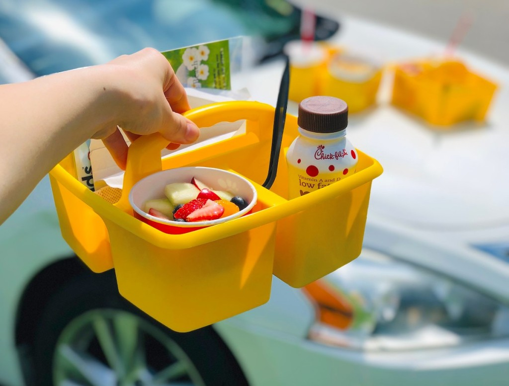 hand holding a yellow caddy with kids meal inside