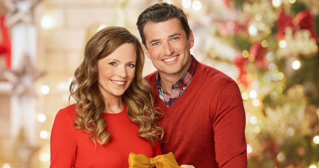 woman and man smiling in front of christmas decor