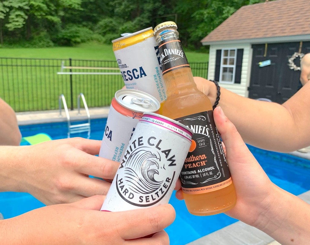 hands holding multiple alcoholic drinks cheers in front of pool