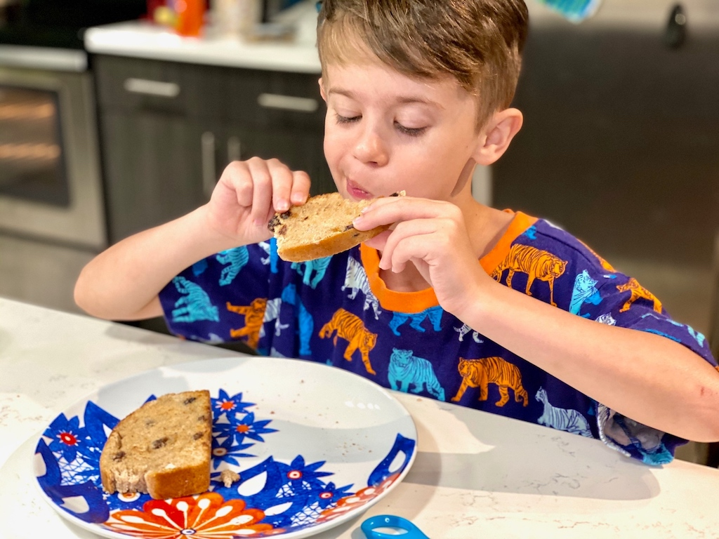 little boy eating homemade bread in kitchen