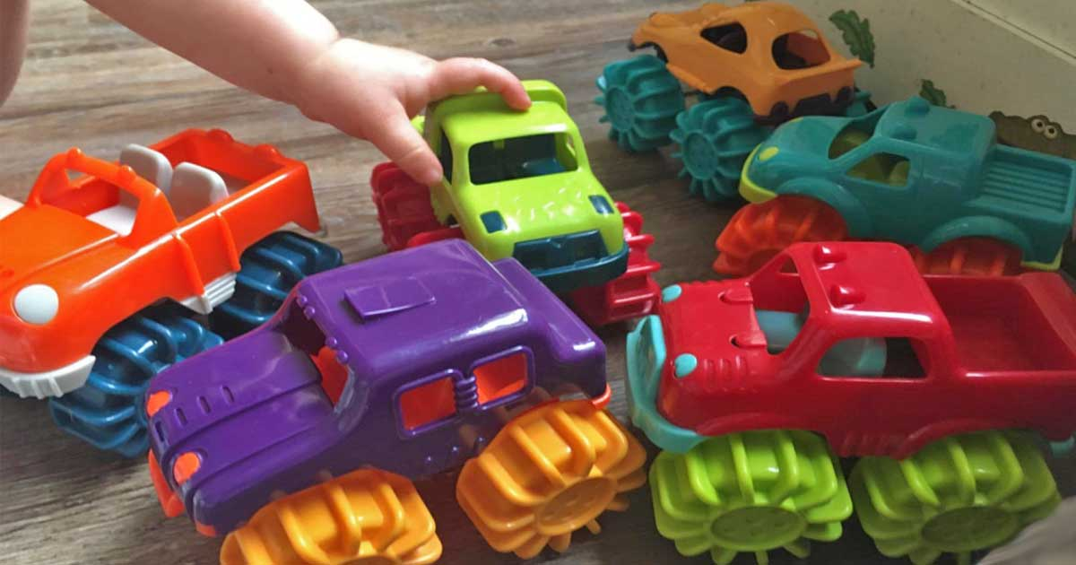 child playing with toy monster trucks on the floor