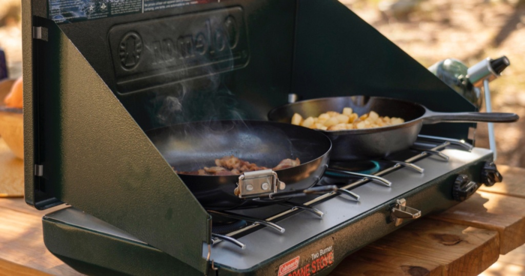 Green Coleman grill with pans heating up food