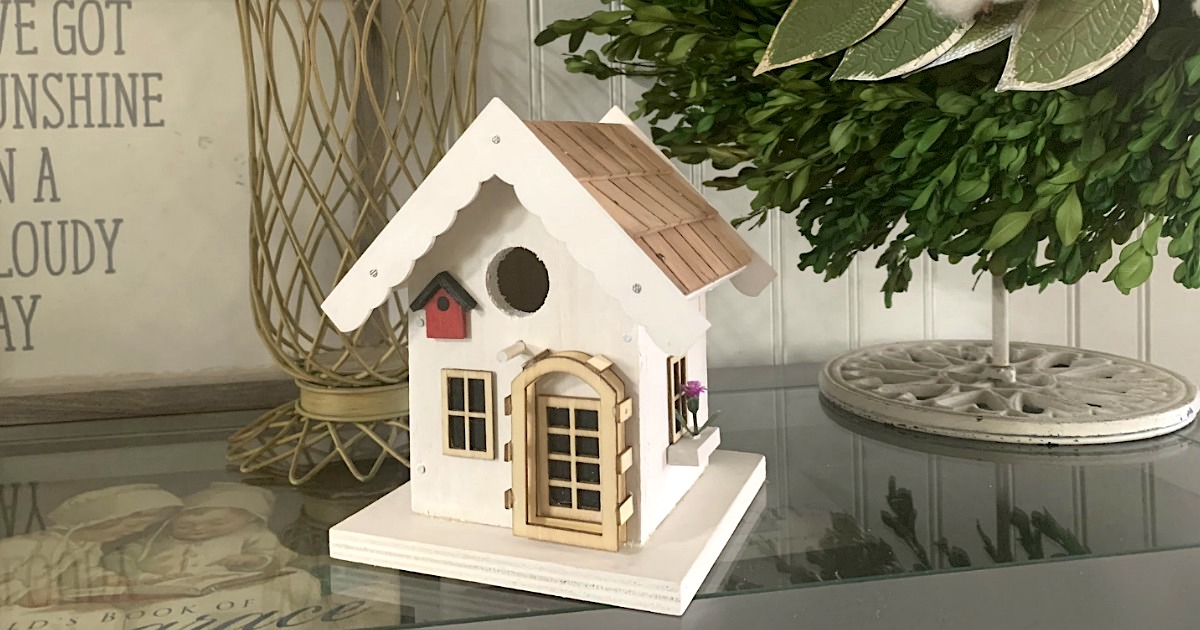 full constructed white birdhouse complete with a door and window sitting on glass table