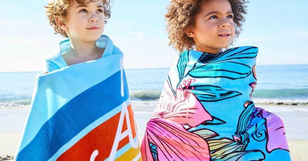 kids wearing disney towels on a beach