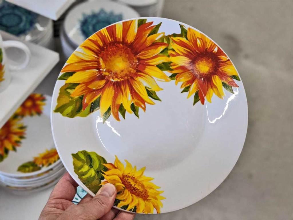 hand holding up a sunflower dinner plate