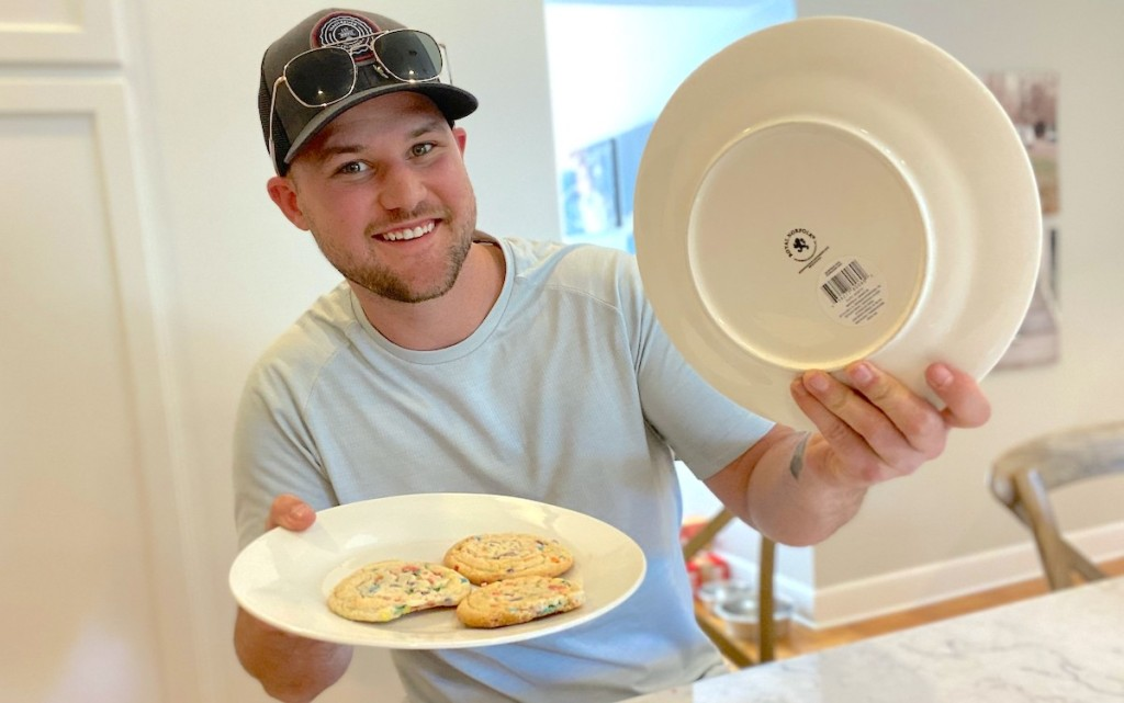 man holding two white plates smiling one with 3 cookies