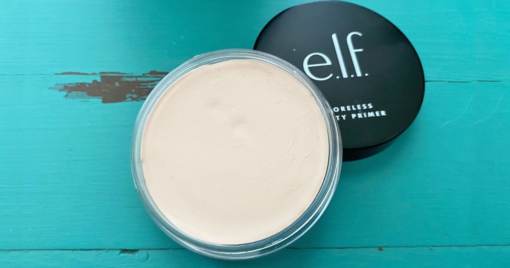 open container of elf poreless putty primer sitting on top of black lid on a blue wooden table
