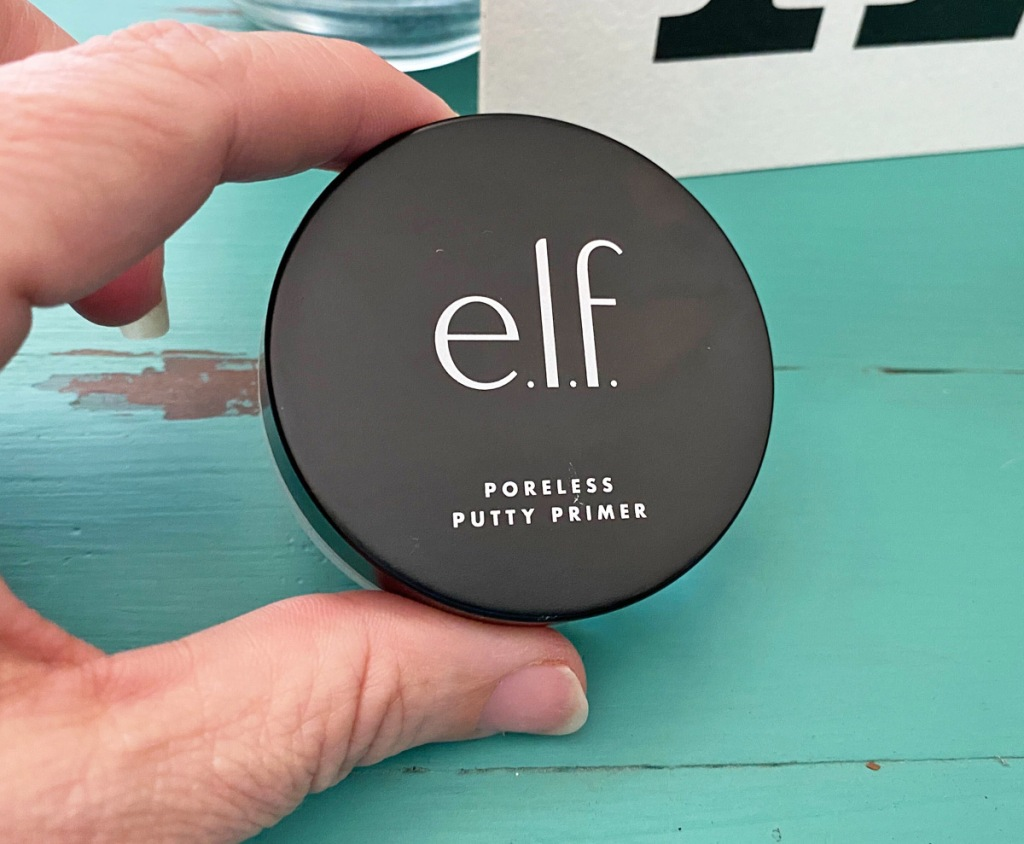 person holding the black lid to the elf poreless putty primer on a blue wooden table