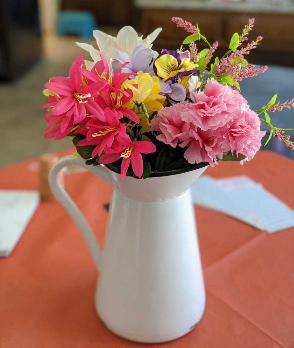 white pitcher vase with colorful faux florals inside