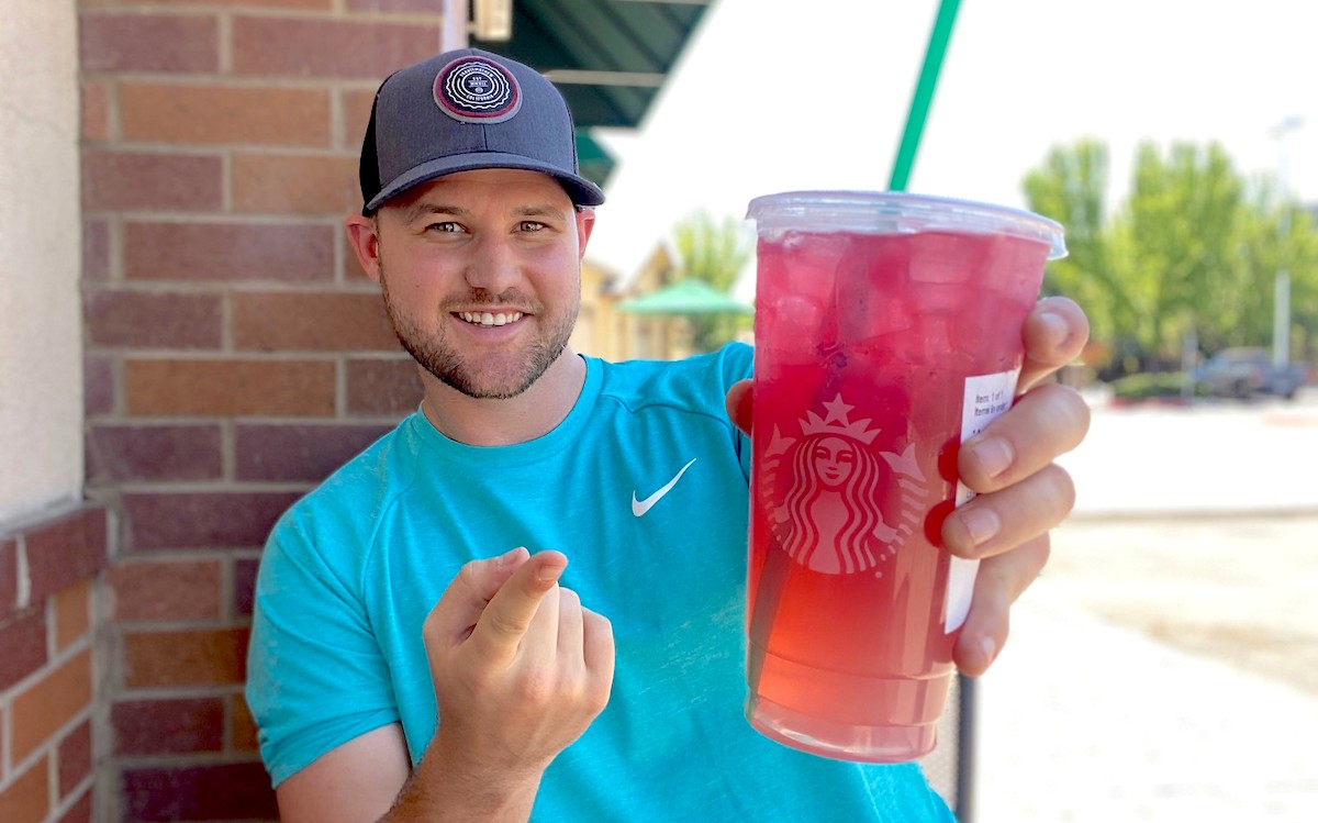 man holding a plastic starbucks cup with red drink inside
