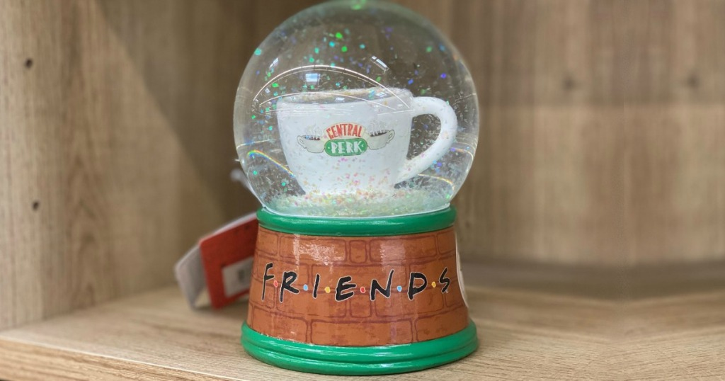 snow globe on shelf with coffee cup in middle