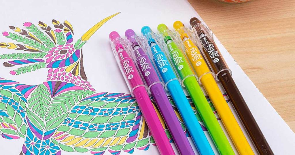 colored pens next to colored bird on a paper