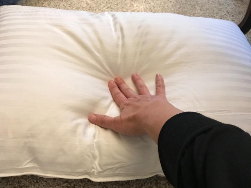 hand pushing down on white pillow