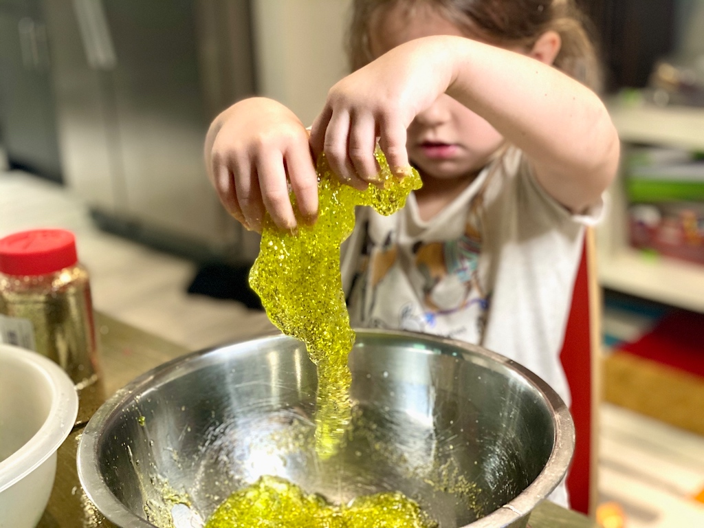 little girl playing with green slime with glitter in bowl