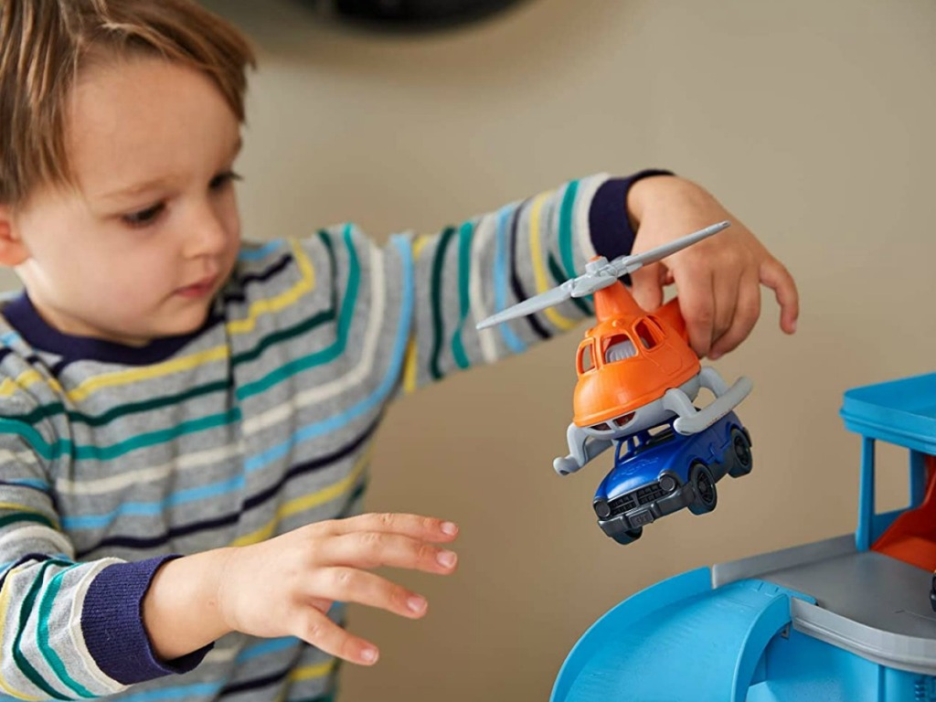 little boy playing with helicopter and car toys