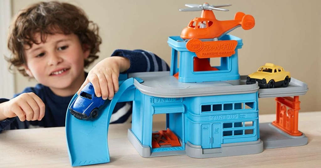 little boy playing with toy that looks like a parking garage