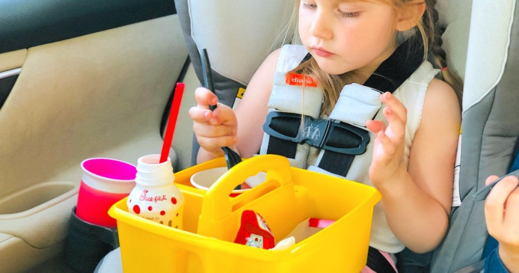 girl sitting in carseat with yellow caddy on lap filled with fast food