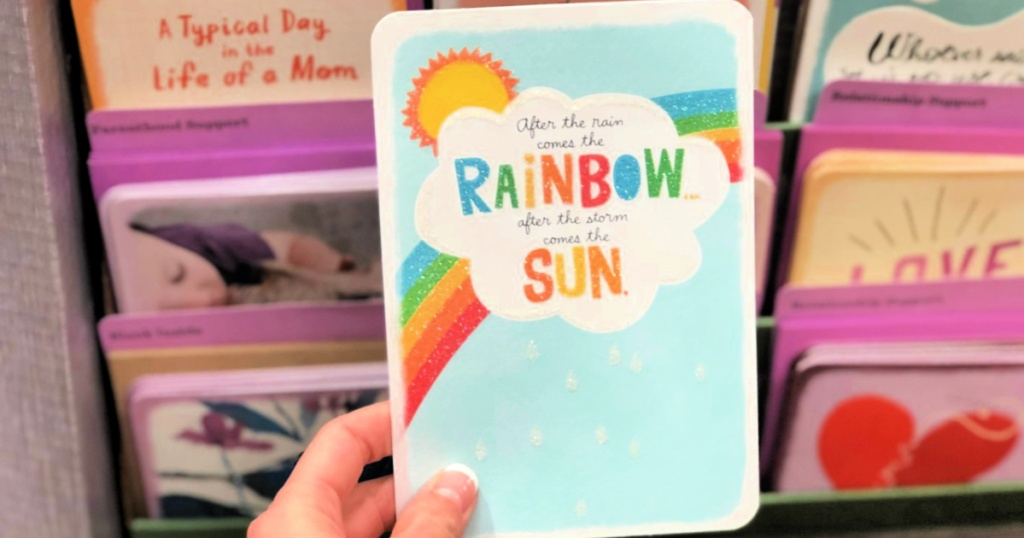 hallmark card in person's hadn with rainbow and thoughtful saying
