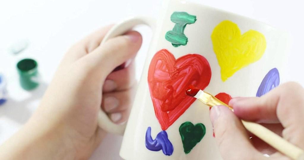 person painting a mug