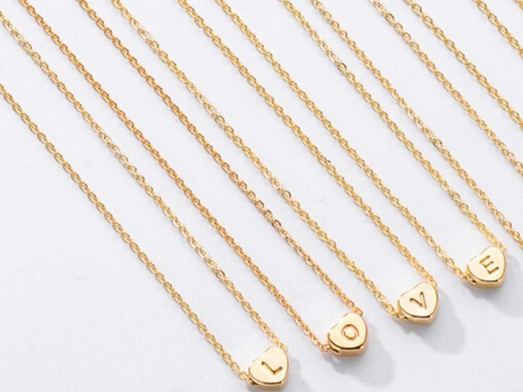 four necklaces with heart pendants on them