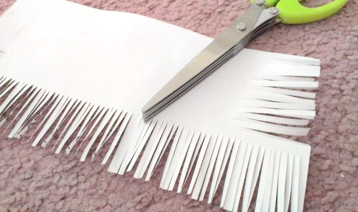 scissors with white sheet of paper shredded on edges