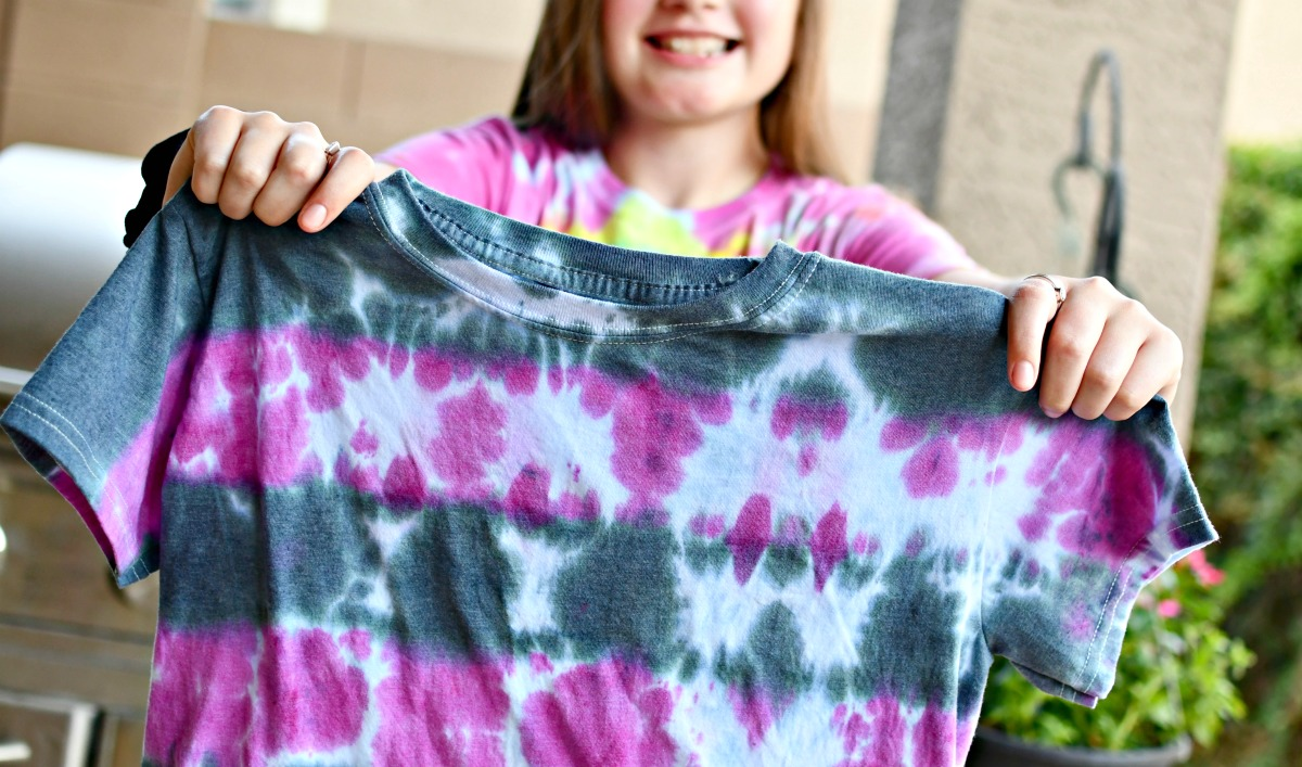 holding up a tye-die shirt