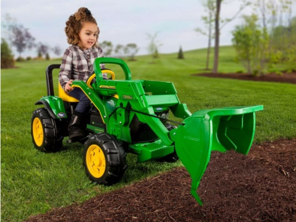 girl on john deere tractor toy digging into dirt pile