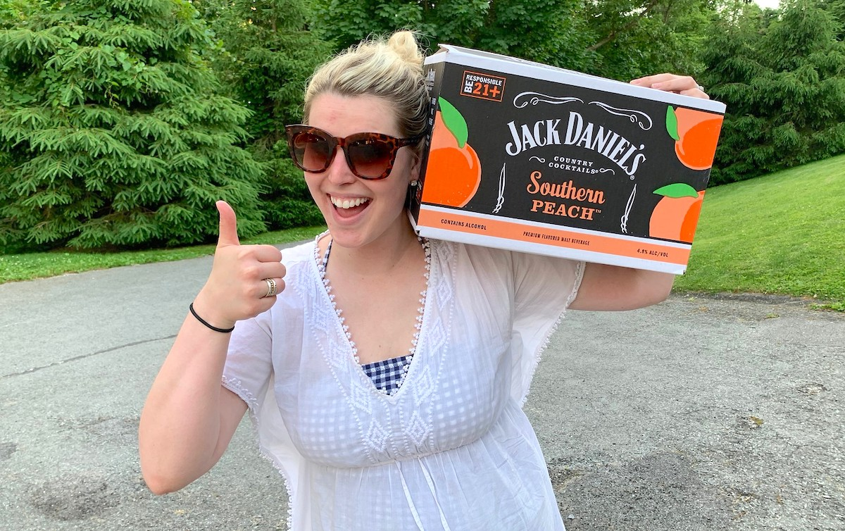 woman holding box of jack daniels refreshers on shoulder giving a thumbs up outside