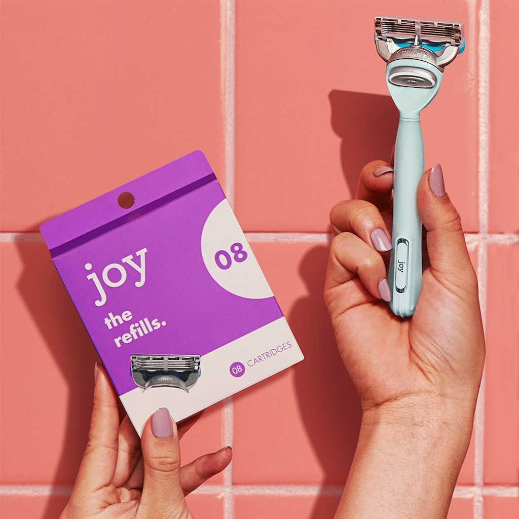 holding up joy razor and refills box