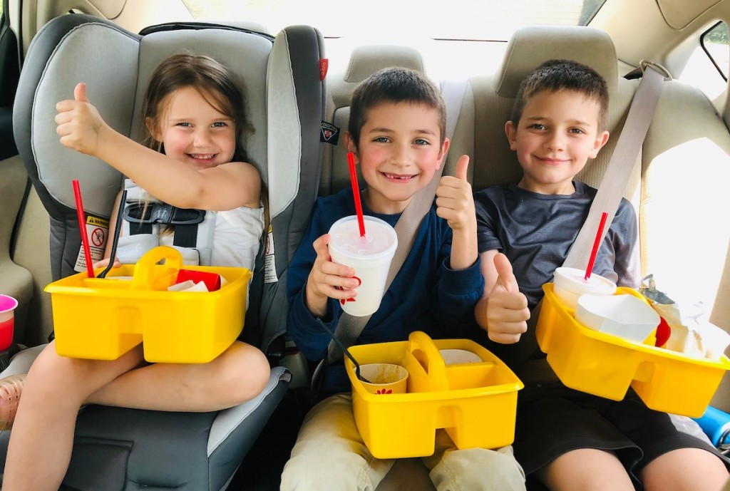 three kids sitting in car with yellow classroom caddies and fast food on lap