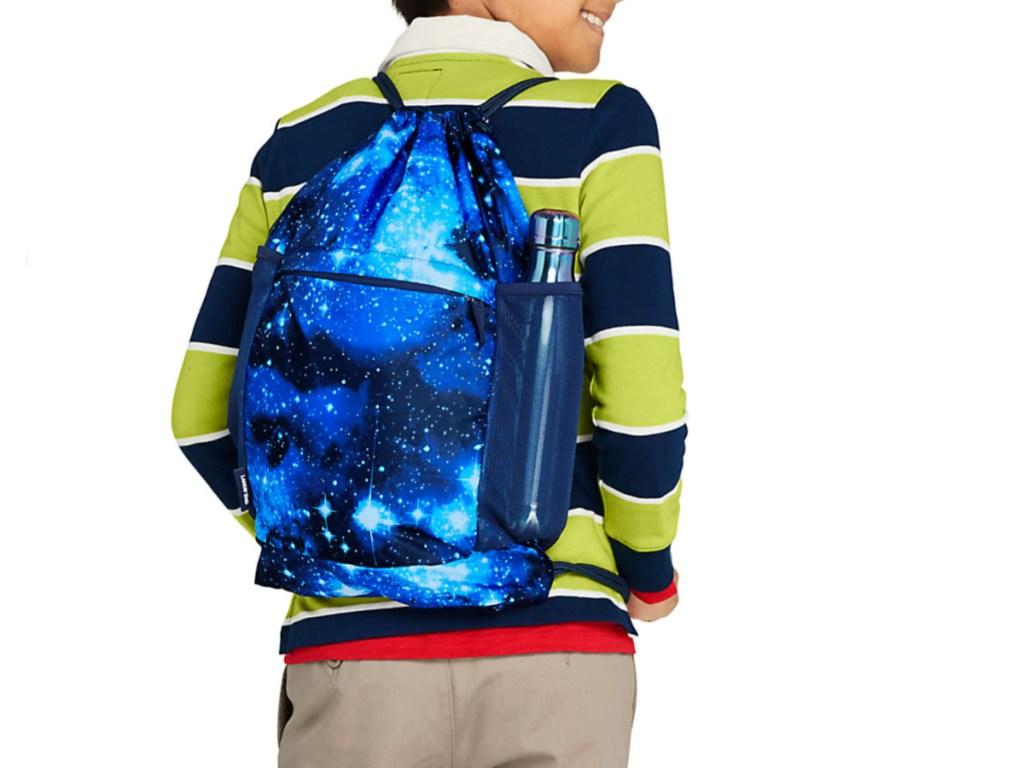 back of boy wearing starry blue cinch bag