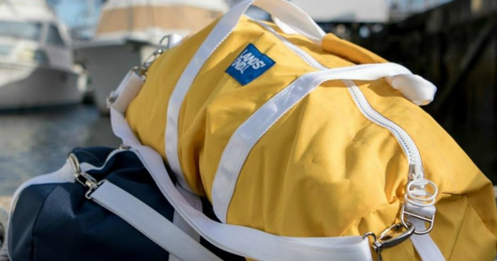 yellow duffle bag sitting on top of blue one near pier
