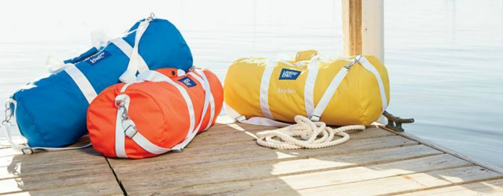 three colorful duffle bags sitting on pier