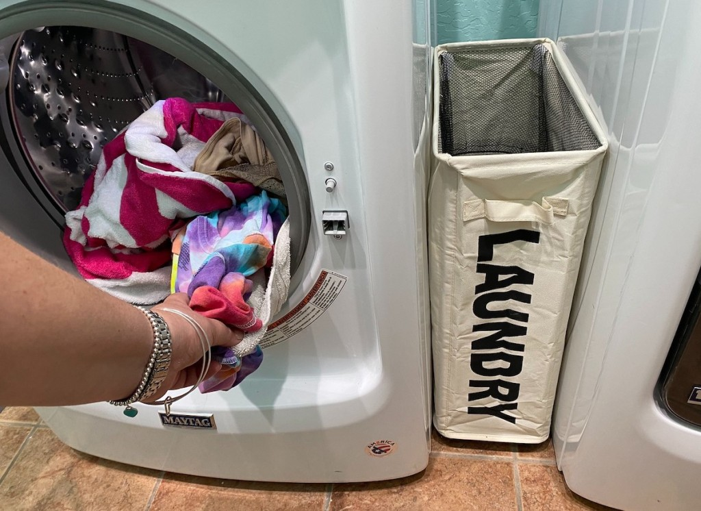hand pulling out laundry from washer with laundry basket next to it