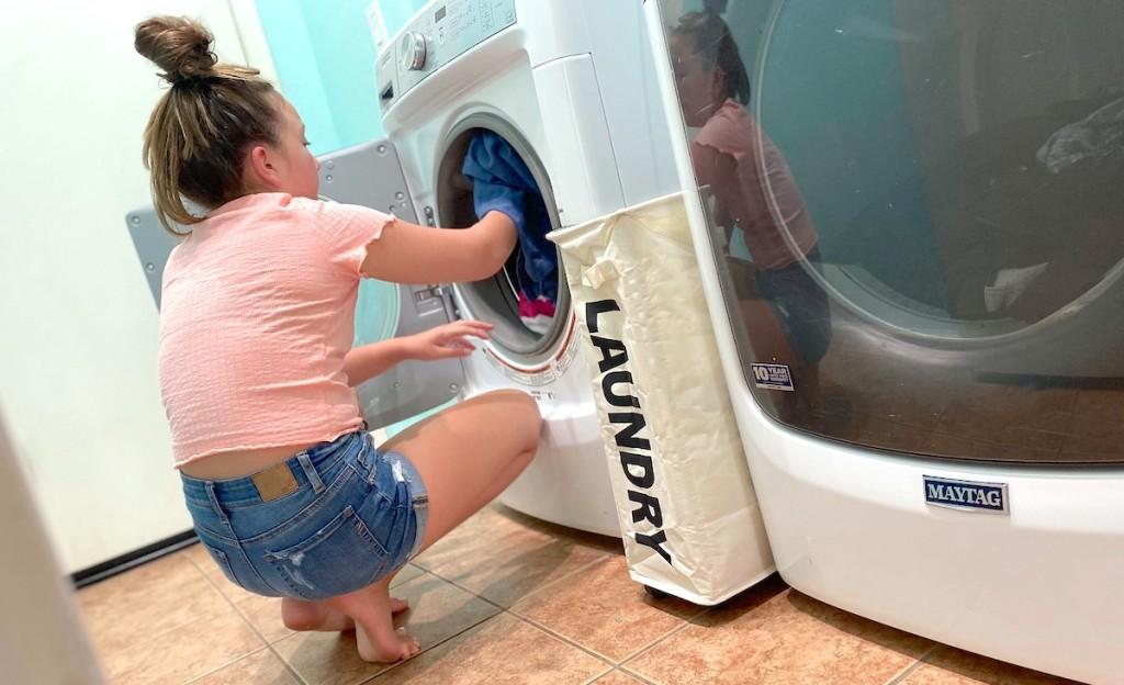 girl loading clothes into washing machine with laundry basket on floor
