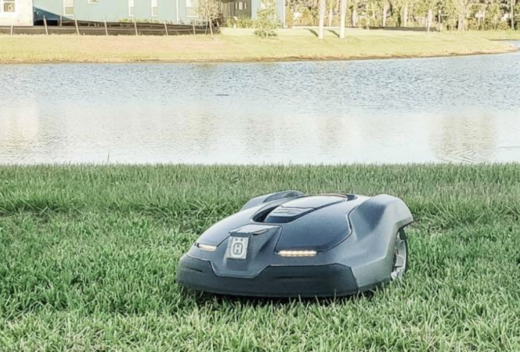 robot lawn mower with lights cutting grass in front of water