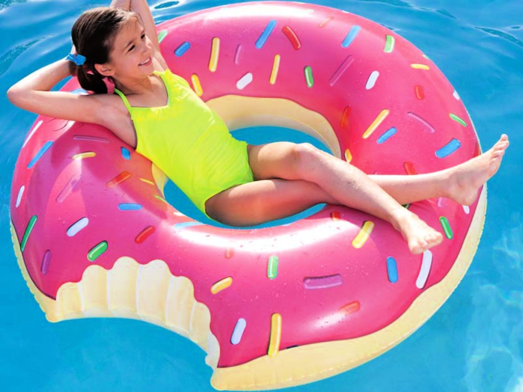little girl laying on an Inflatables Giant Pool Float Donut