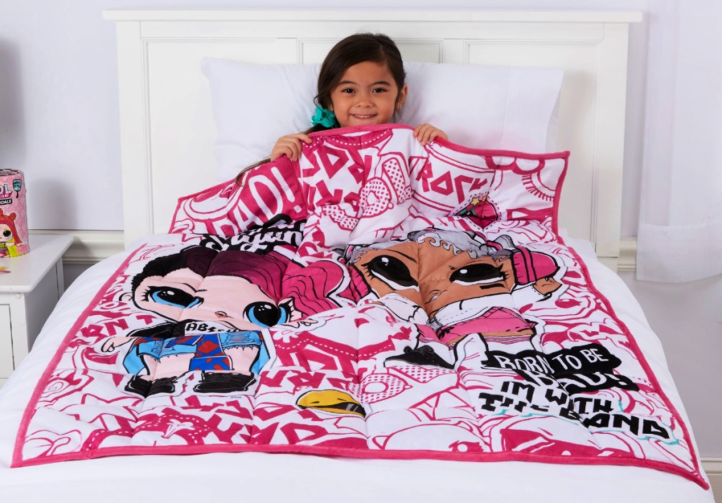 little girl sitting on bed with an L.O.L. Surprise! Kids 4.5lb Weighted Blanket