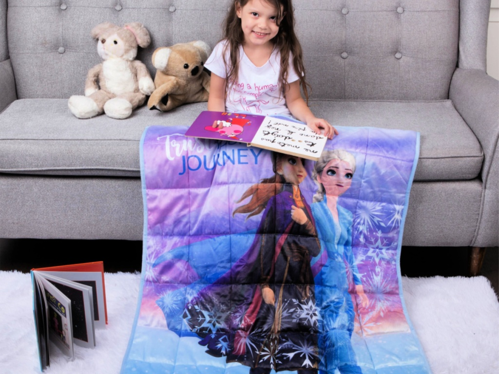 little girl sitting on couch with Disney's Frozen 2 Kids 4.5lb Weighted Blanket