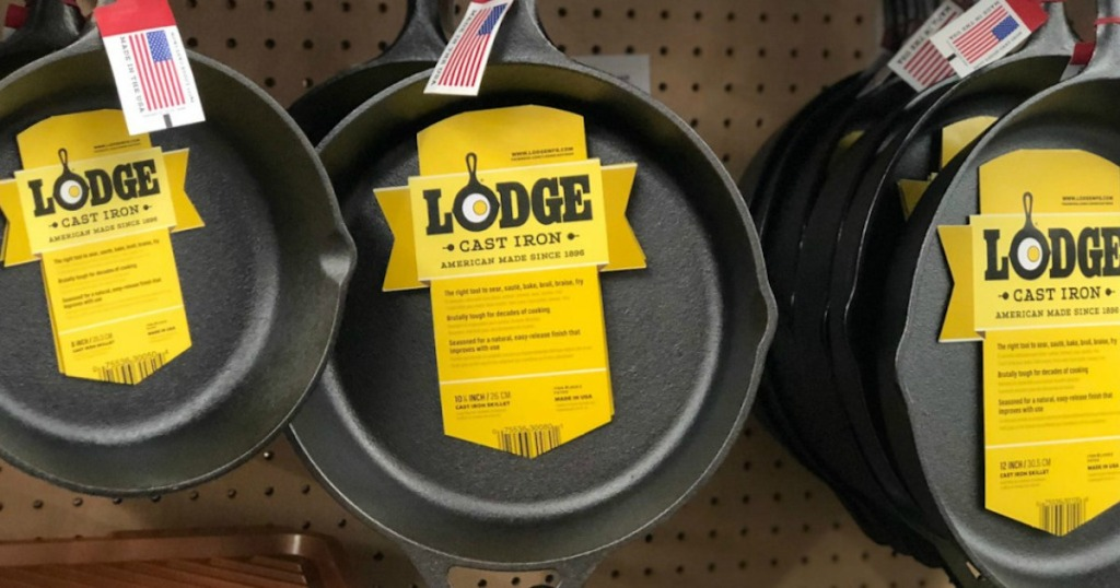 three lodge cast iron skillets hanging on display in store
