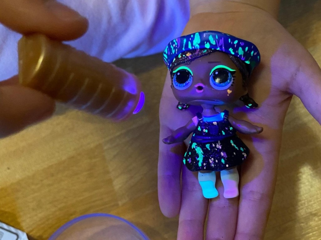 hand holding doll under black light with glow-in-the dark accents