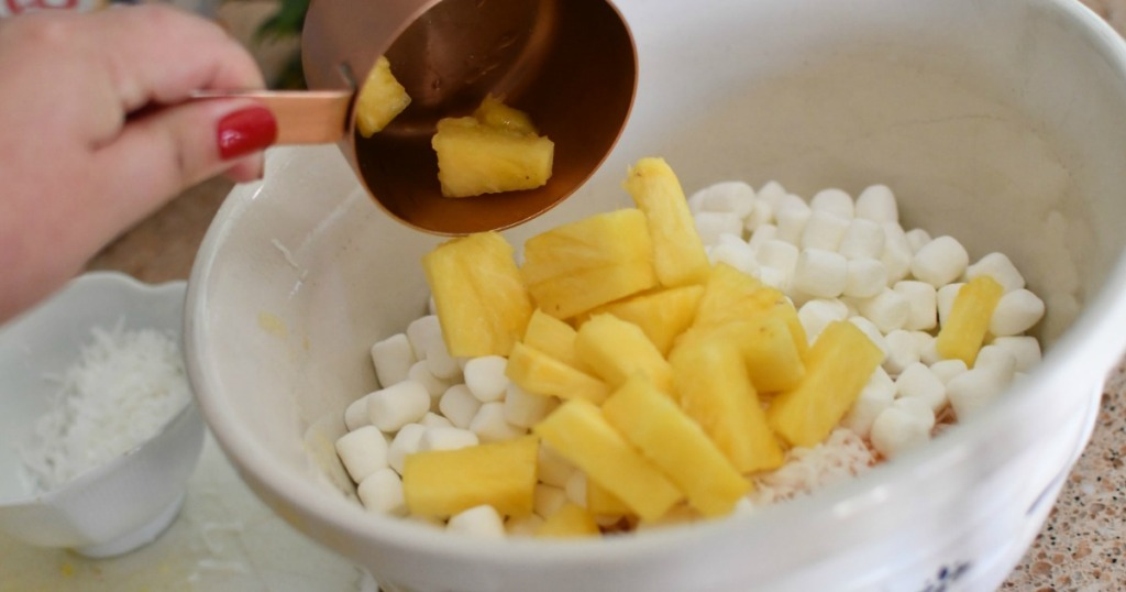 making pineapple fluff salad with pinapples and marshmallows