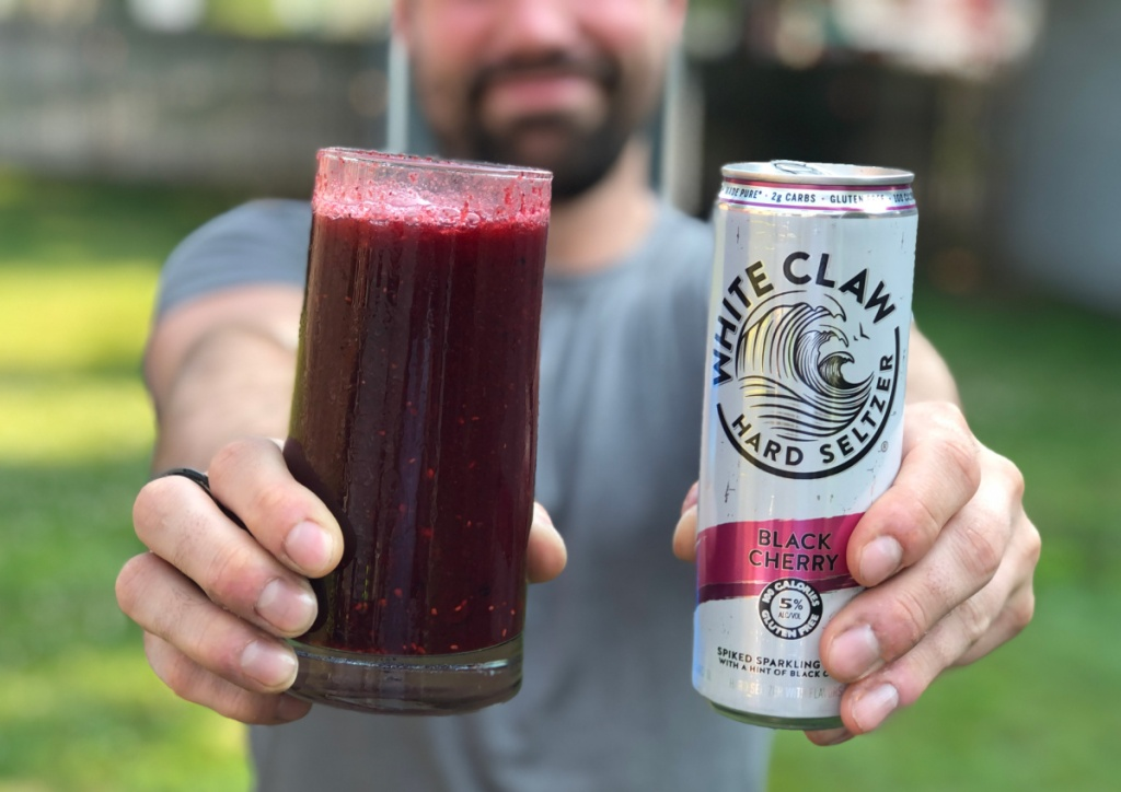 man holding up can of white claw and slushie