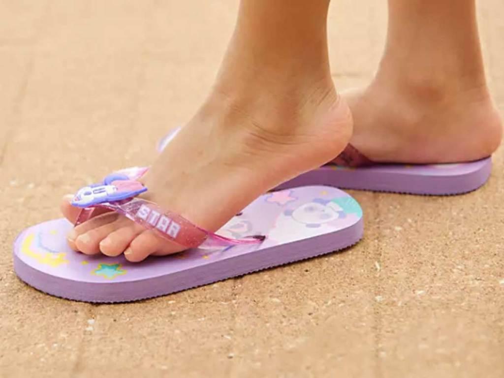 girl wearing purple flip flops on the beach