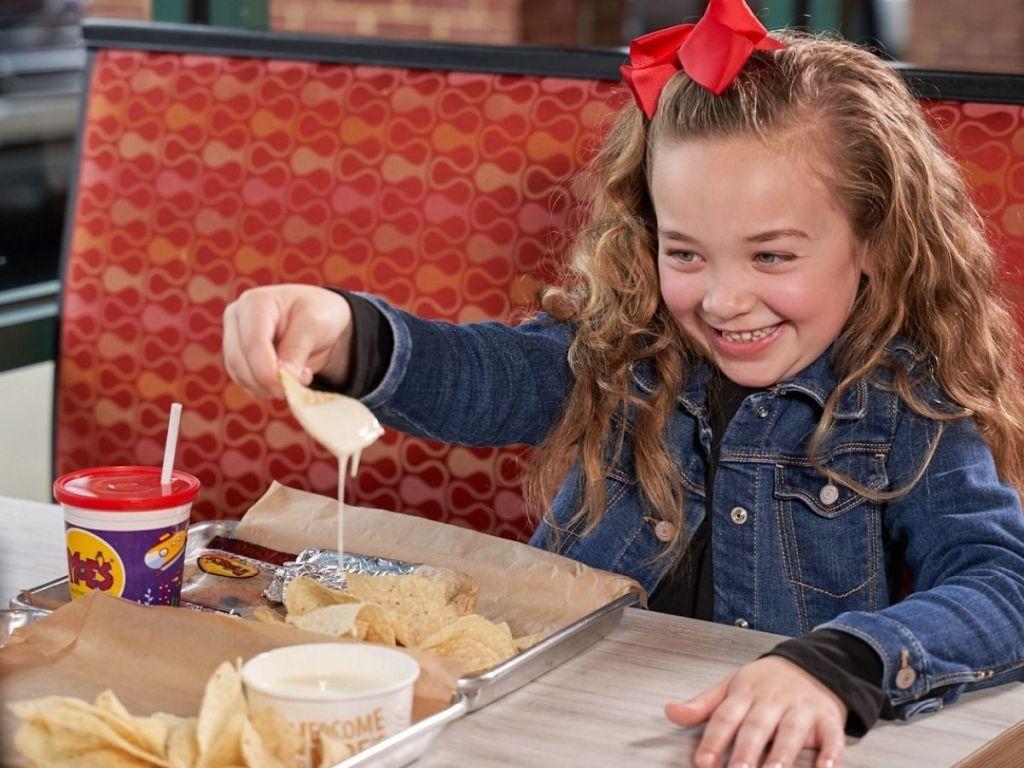 little girl eating moe's nachos