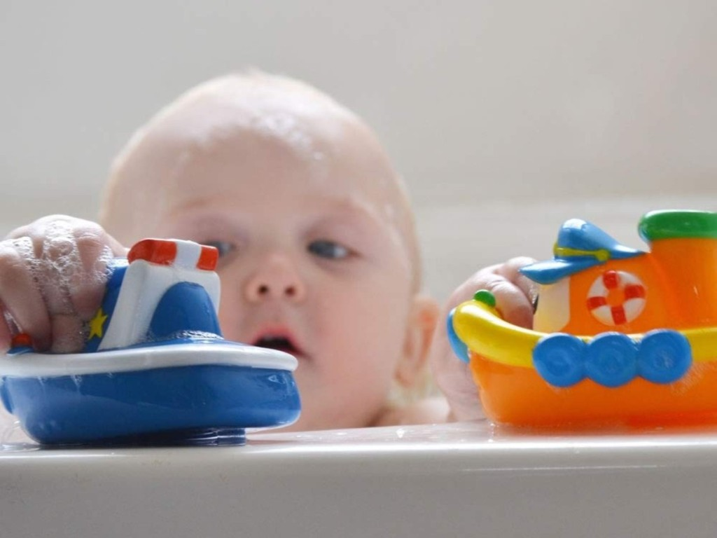 baby playing with toy boats in bathtub