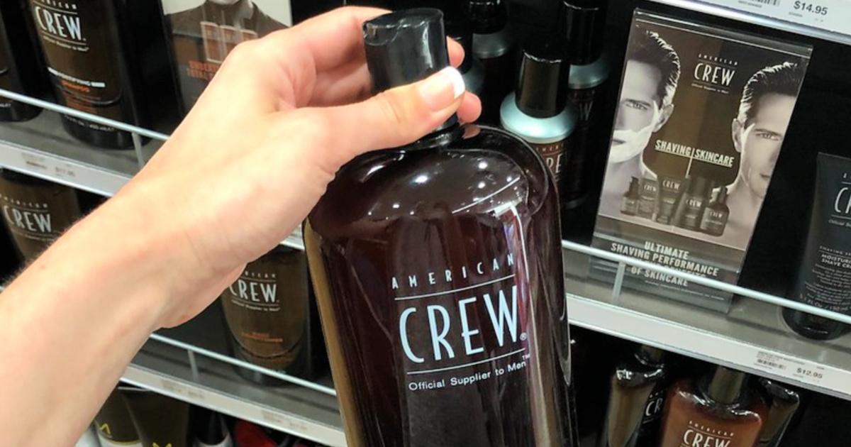 person holding american crew shampoo bottle