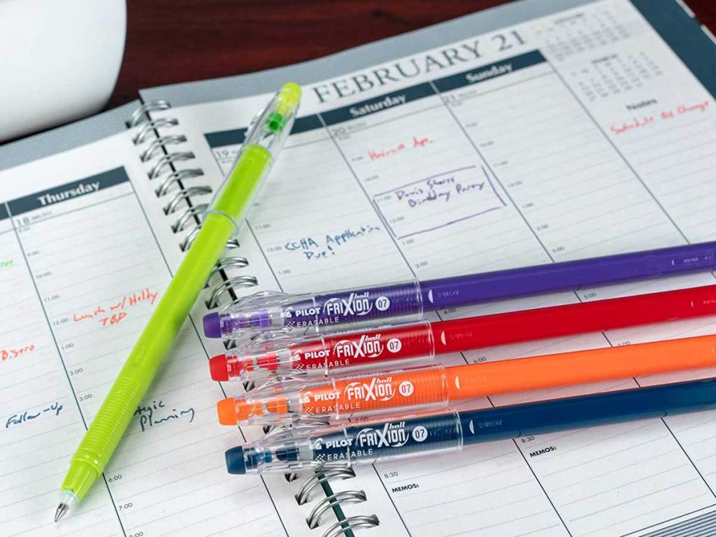 colored pens laying on a desktop calendar