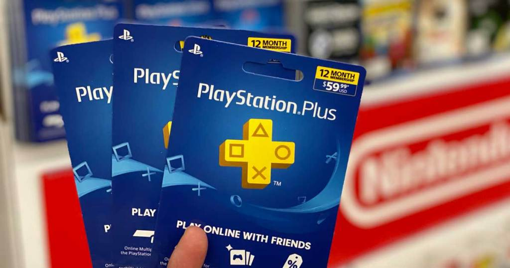 hand holding two playstation plus cards