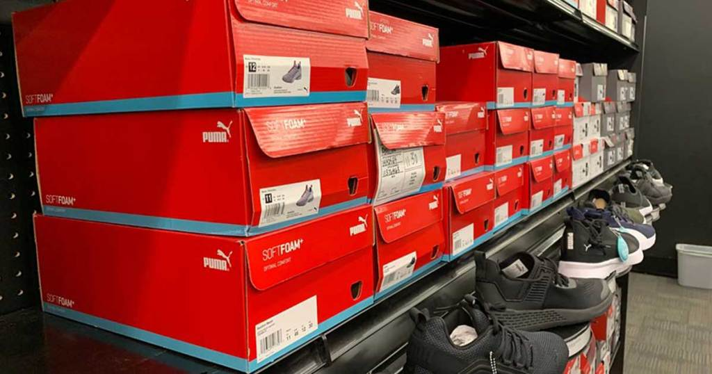 puma shoes in boxes on display shelf at store
